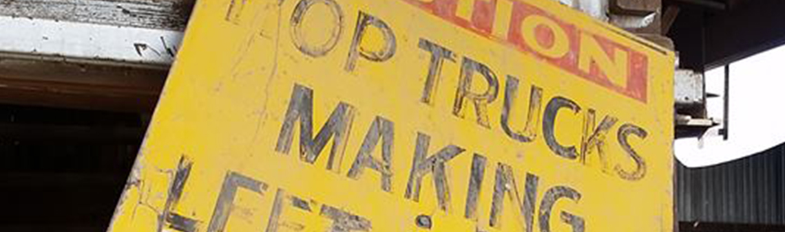 Photo of a sign saying hop trucks making left turn. Purely decorative for the hop news page